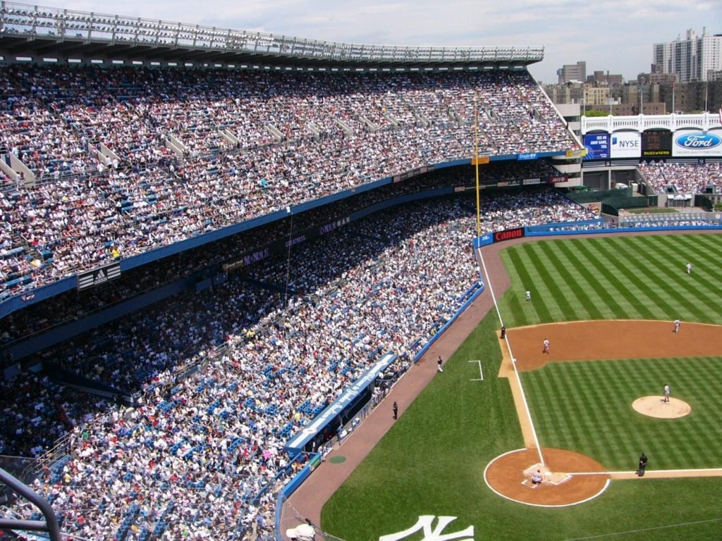 A photograph of a baseball stadium with lots of people in it. Secretly, I'm not there.